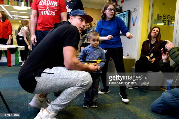 Rob Gronkowski shows Joey how to shoot a dart gun during an Olympic dart shooting contest at Boston Children's Hospital on February 13 2018 in Boston...