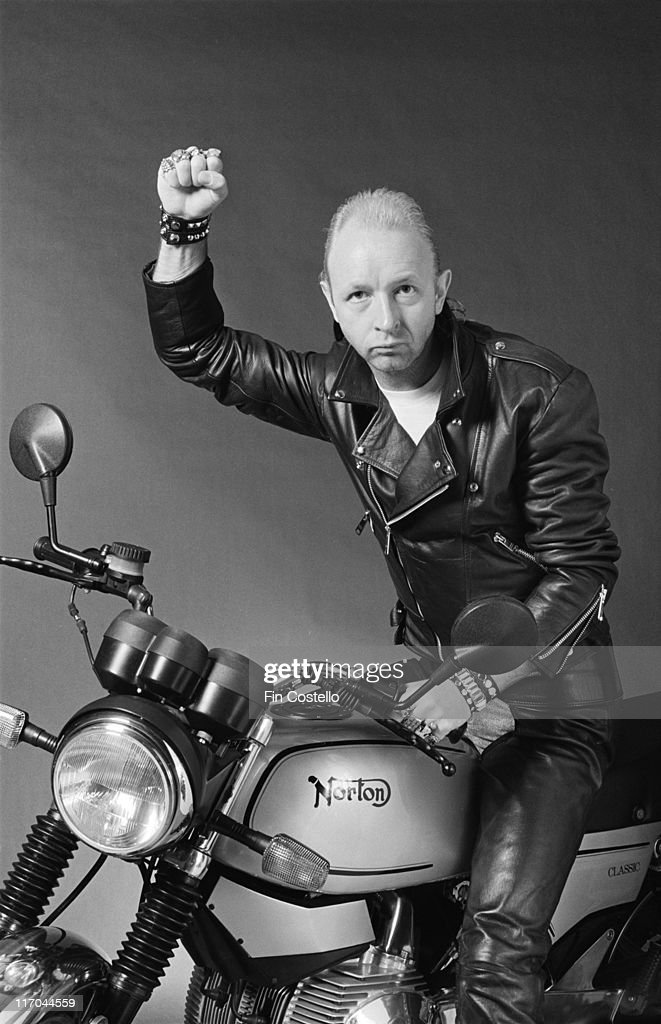 Rob Halford, British singer-songwriter with heavy metal band Judas Priest, raising a fist triumphantly while posing on a Norton motorcycle, on the Southbank, London, England, Great Britain, 1990.