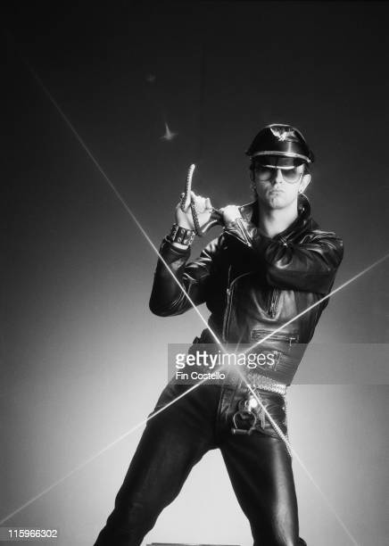 Rob Halford singer with British heavy metal band Judas Priest poses wearing black leather clothing and holding a whip in a studio portrait circa 1978...