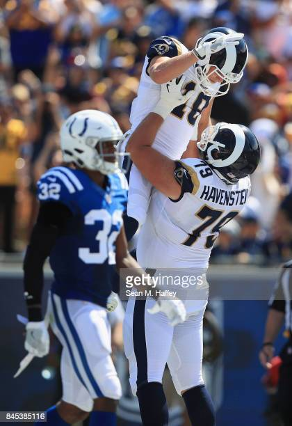 Rob Havenstein congratulates Cooper Kupp of the Los Angeles Rams after his touchdown while T.J. Green of the Indianapolis Colts looks on during the...