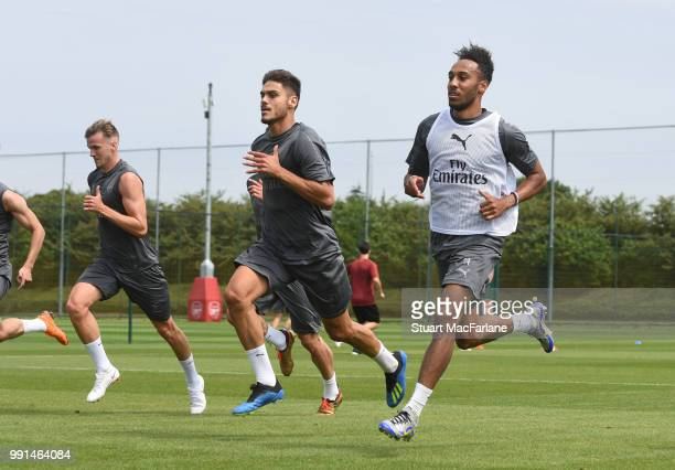 Rob Holding Konstantinos Mavropanos and PierreEmerick Aubameyang of Arsenal run during a training session at London Colney on July 4 2018 in St...