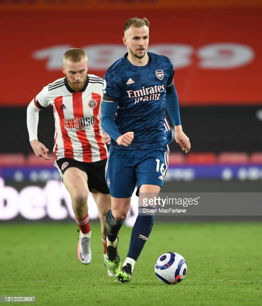 Rob Holding of Arsenal breaks past Oli McBurnie of Sheffield United during the Premier League match between Sheffield United and Arsenal at Bramall...