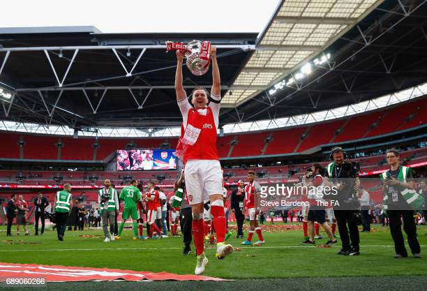 Rob Holding of Arsenal celebrates with the trophy after the Emirates FA Cup Final between Arsenal and Chelsea at Wembley Stadium on May 27, 2017 in...