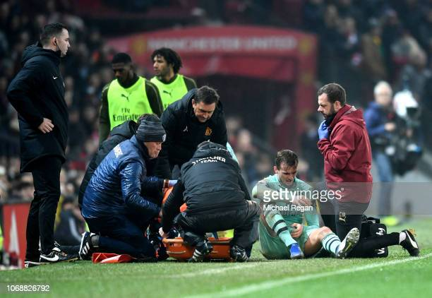 Rob Holding of Arsenal receives medical treatment during the Premier League match between Manchester United and Arsenal FC at Old Trafford on...