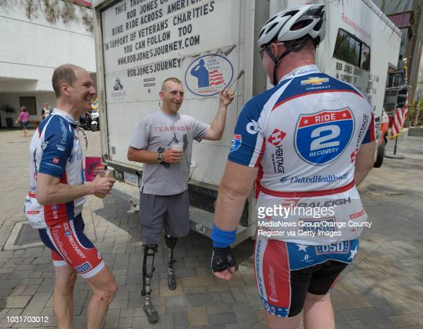 Rob Jones a double amputee Marine veteran who lost both legs in Afghanistan chats with fellow riders Ray Clark left and Hugh McLarnon after riding to...