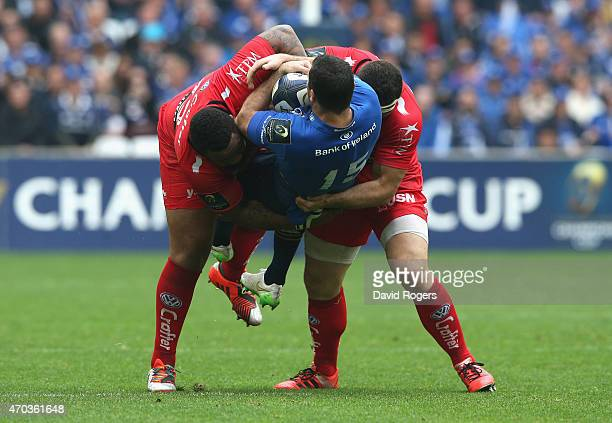 Rob Kearney of Leinster is tackled by Mathieu Bastareaud and Guilhem Guirado during the European Rugby Champions Cup semi final match between RC...