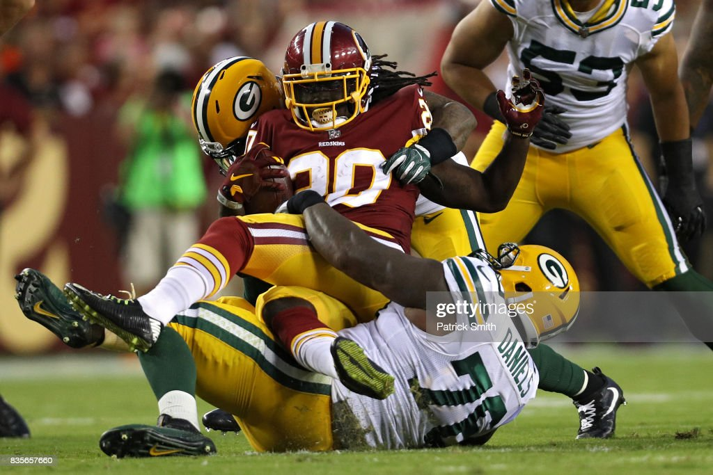 Rob Kelley #20 of the Washington Redskins is tackled by Green Bay Packers defenders in the first half during a preseason game at FedExField on August 19, 2017 in Landover, Maryland.