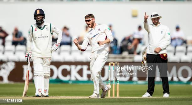 Rob Keogh of Northamptonshire celebrates after taking the wicket of Joe Leach of Worcestershire as Moeen Ali of Worcestershire looks on during the...