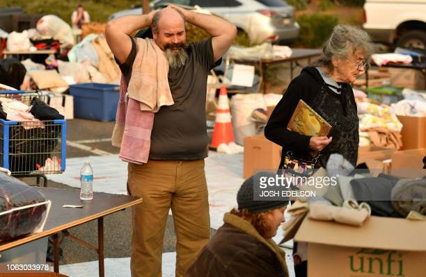Rob Lowe sighs while searching through donated clothing at an evacuee encampment in a Walmart parking lot in Chico California on November 17 2018...