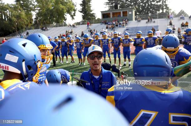 Rob Mendez the head coach for the Prospect High School Junior Varsity football team talks to his team in the huddle during their first game of the...