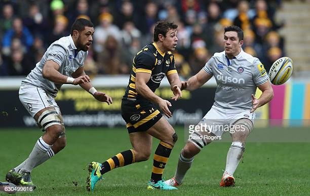 Rob Miller of Wasps passes the ball watched by Taulupe Faletau and Francois Louw during the Aviva Premiership match between Wasps and Bath Rugby at...