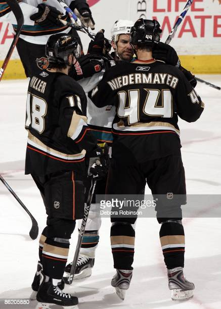 Rob Niedermayer and Andrew Ebbett of the Anaheim Ducks scrum with Dan Boyle of the San Jose Sharks during Game Four of the Western Conference...