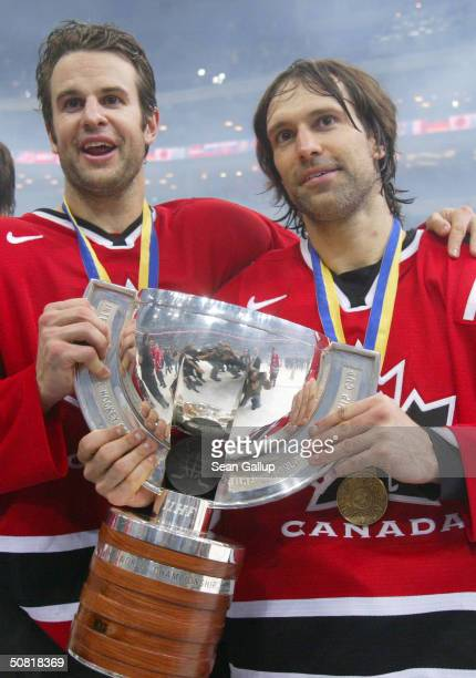 Rob Niedermayer and Scott Niedermayer of Canada hold up the trophy after winning the Finals against Sweden at the International Ice Hockey Federation...
