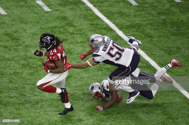 Rob Ninkovich of the New England Patriots reaches to tackle Devonta Freeman of the Atlanta Falcons during the first quarter during Super Bowl 51 at...