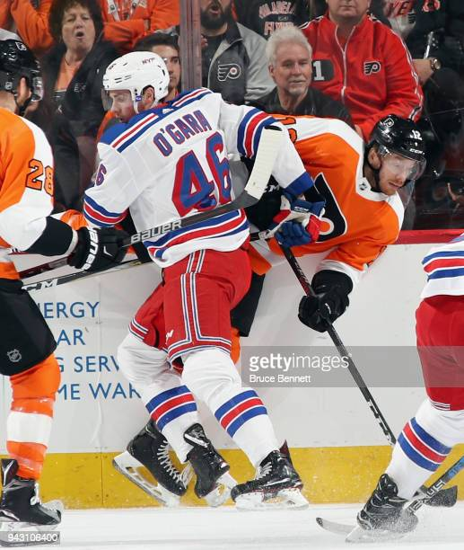 Rob O'Gara of the New York Rangers hits Michael Raffl of the Philadelphia Flyers into the boards during the first period at the Wells Fargo Center on...