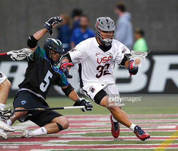 Rob Pannell of Team USA gets by Jordan Burke of Team MLL in the first quarter during the 2014 MLL All Star Game at Harvard Stadium on June 26 2014 in...