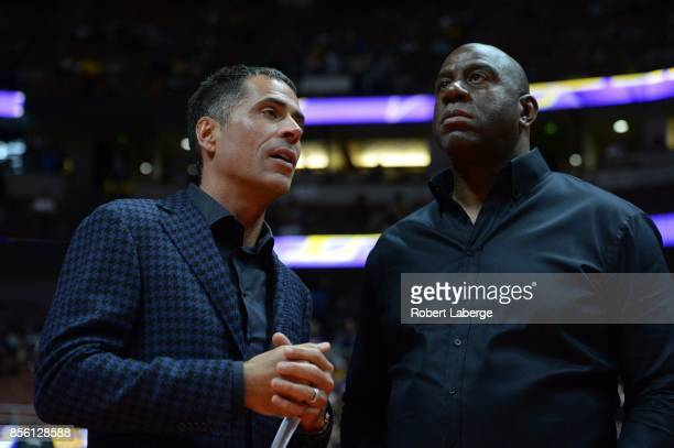 Rob Pelinka general manager of the Los Angeles Lakers talks to Earvin Magic Johnson president of basketball operations of the Lakers before the game...