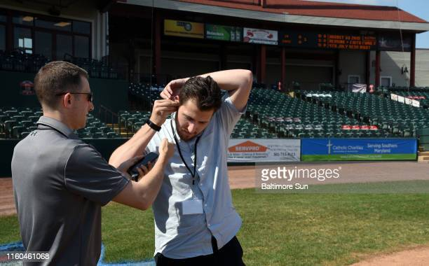Rob Porter, left, TrackMan operator for Major League Baseball, fits Baltimore Sun baseball writer Nathan Ruiz, right, with an earpiece for the new...