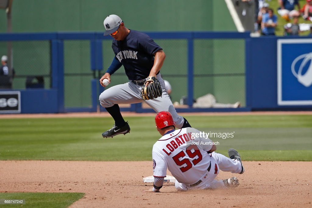Rob Refsnyder #38 of the New York Yankees is unable to turn the double play as Jose Lobaton #59 of the Washington Nationals slides into second base in the fourth inning during a spring training game at The Ballpark of the Palm Beaches on March 20, 2017 in West Palm Beach, Florida. The Yankees defeated the Nationals 9-3.