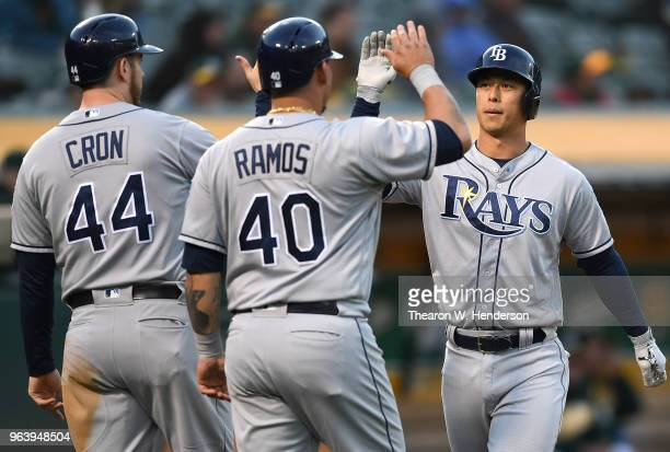 Rob Refsnyder of the Tampa Bay Rays is congratulated by CJ Cron and Wilson Ramos after Refsnyder hit a threerun home run against the Oakland...