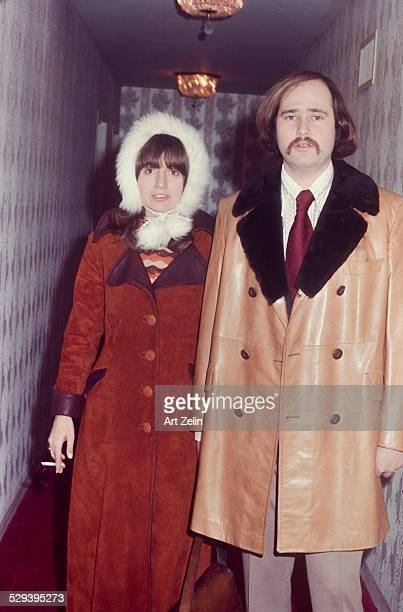 Rob Reiner with his wife Penny Marshall in a hallway He is wearing a fur trimmed leather coat she is wearing a rust colored suede coat and fur hat...