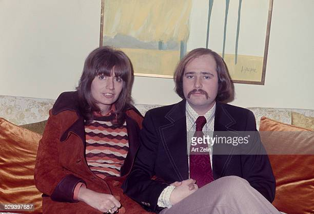 Rob Reiner with his wife Penny Marshall sitting on a sofa She is wearing a rust suede coat circa 1970 New York