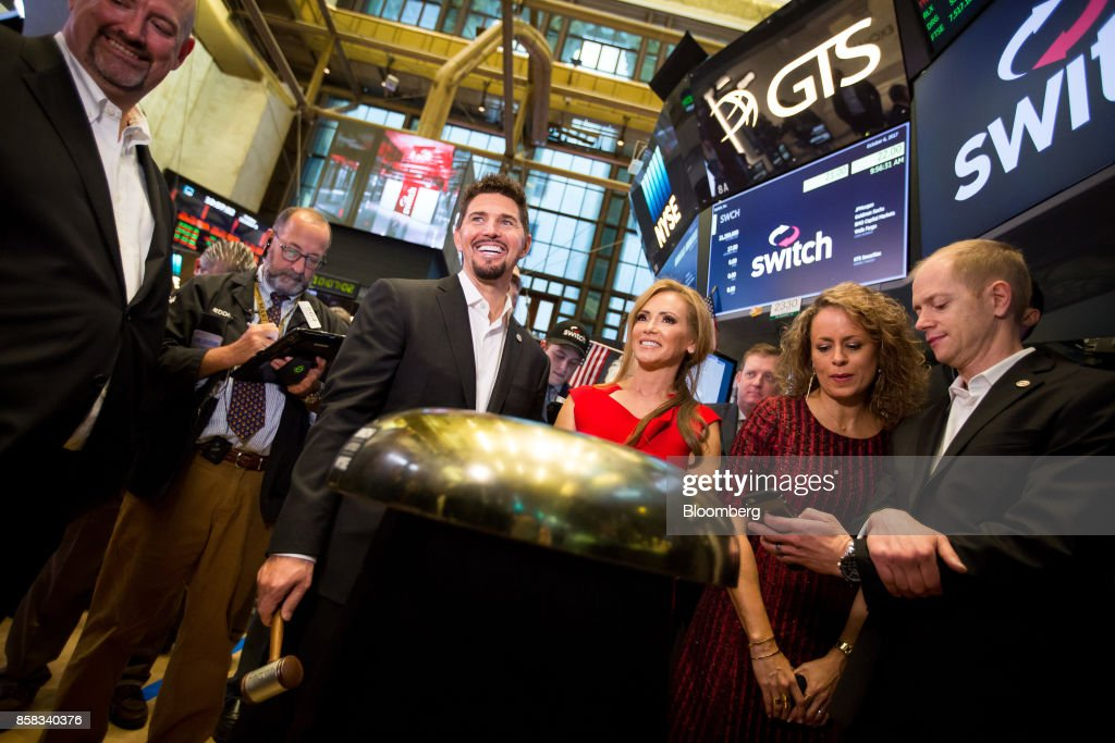 Rob Roy, founder and chief executive officer of Switch Inc., center left, smiles during the company's initial public offering (IPO) on the floor of the New York Stock Exchange (NYSE) in New York, U.S., on Friday, Oct. 6, 2017. Switchjumped by almost half in its trading debut after raising $531 million in an initial public offering, the third-biggest technology IPO this year in the U.S.. Photographer: Michael Nagle/Bloomberg via Getty Images