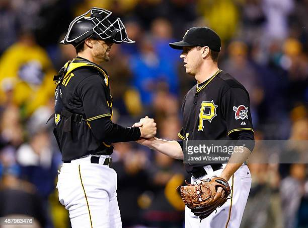 Rob Scahill of the Pittsburgh Pirates is congratulated by teammate Chris Stewart following their 102 win in the 9th inning against the Milwaukee...