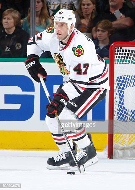 Rob Scuderi of the Chicago Blackhawks handles the puck against the Dallas Stars at the American Airlines Center on December 22 2015 in Dallas Texas