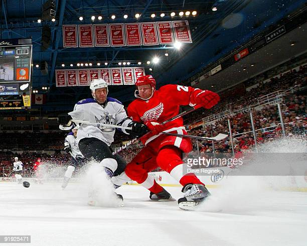 Rob Scuderi of the Los Angeles Kings and Jason Williams of the Detroit Red Wings battle for the puck during a NHL game at Joe Louis Arena on October...