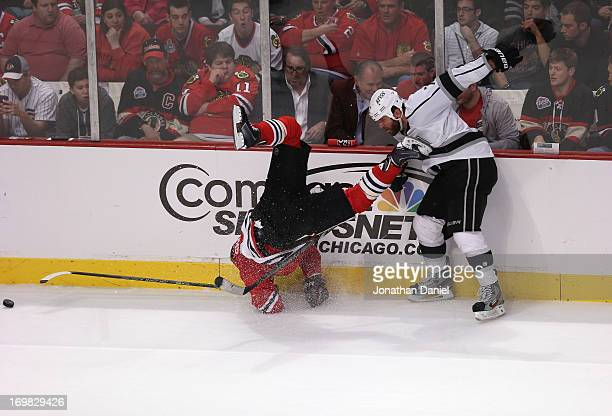 Rob Scuderi of the Los Angeles Kings checks Patrick Sharp of the Chicago Blackhawks along the side boards in the second period of Game Two of the...