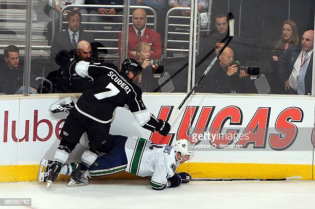 Rob Scuderi of the Los Angeles Kings throws a check against Alexandre Burrows of the Vancouver Canucks in Game Three of the Western Conference...