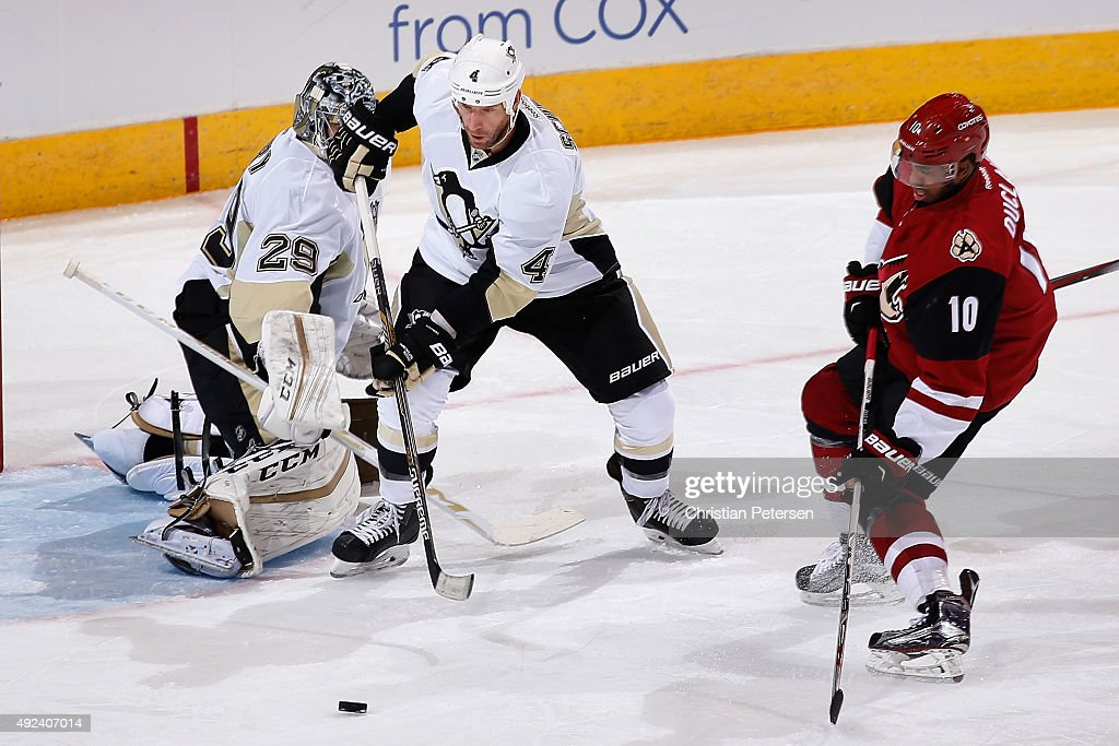 Rob Scuderi #4 of the Pittsburgh Penguins attempts to clear the puck ahead of goaltender Marc-Andre Fleury #29 as Anthony Duclair #10 of the Arizona Coyotes skates in during the NHL game at Gila River Arena on October 10, 2015 in Glendale, Arizona.