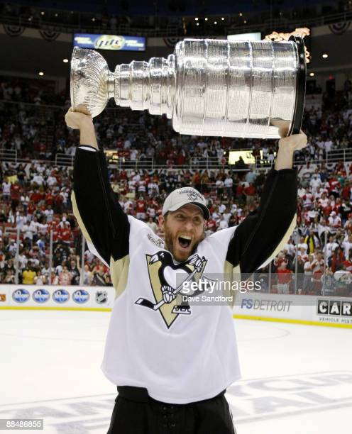 Rob Scuderi of the Pittsburgh Penguins hoists the Stanley Cup following a 21 victory over the Detroit Red Wings during Game Seven of the 2009 Stanley...