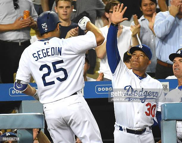 Rob Segedin of the Los Angeles Dodgers is greeted by manager Dave Roberts after a solo home run in the second inning of the game against the San...