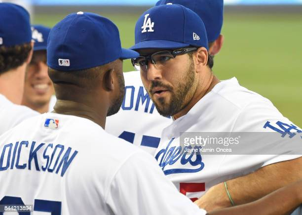 Rob Segedin of the Los Angeles Dodgers talks with O'Koyea Dickson of the Los Angeles Dodgers in the dugout during the game against the Arizona...