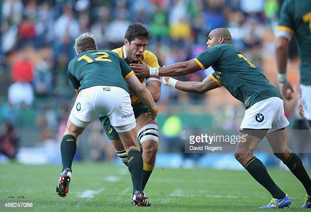 Rob Simmons of the Wallabies is tackled by Jean de Villiers and Cornal Hendricks during The Rugby Championship match between the South African...