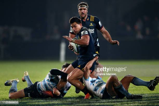 Rob Thompson of the Highlanders is tackled by Adam AshleyCooper and Nick Phipps of the Waratahs during the round 18 Super Rugby match between the...