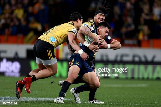 Rob Thompson of the Highlanders is tackled by Ardie Savea of the Hurricanes during the round 16 Super Rugby match between the Highlanders and the...