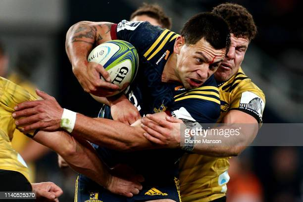 Rob Thompson of the Highlanders is tackled by Ricky Riccitelli of the Hurricanes during the round 8 Super Rugby match between the Highlanders and...