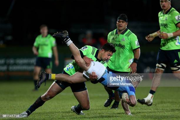 Rob Thompson of the Highlanders tackles Arthur Retiere of the French Barbarians during the match between the Highlanders and the French Barbarians at...