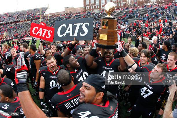 Rob Trigg of the Cincinnati Bearcats holds the the Big East Championship Trophy as he celebrates with fans and teammates after the Bearcats defeated...