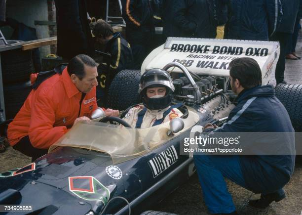Rob Walker Racing Team owner, Rob Walker talks to British Formula One racing driver Graham Hill sitting in the driver's seat of the Brooke Bond Oxo...