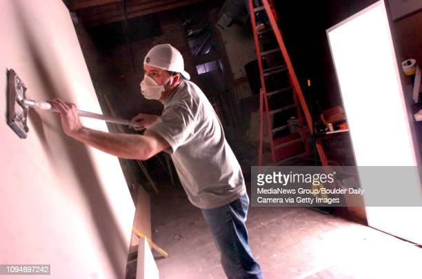 Rob Walters of Drywall Partitions sands down a wall at the Wenger shop that will be opening on the 1100 block of the Pearl Street Mall in Boulder