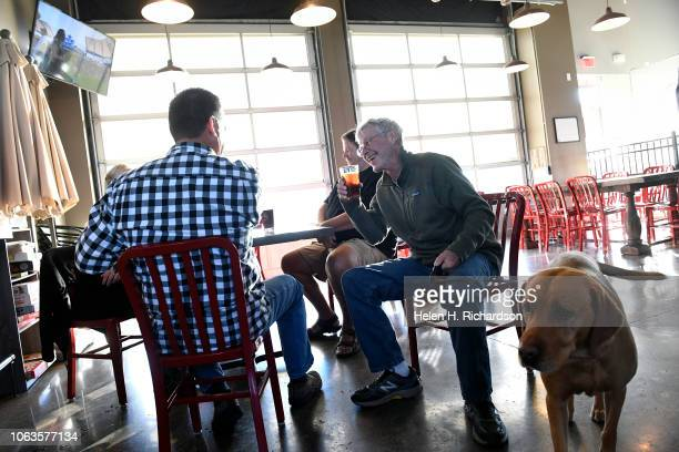 Rob Ward left and George who did not want his last name used enjoy beer with friends and George's dog Sonny a Fox Red Labrador retriever right at...