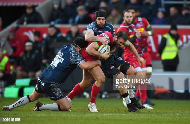 Rob Webber and Bryn Evans of Sale Sharks tackle Jamie Roberts of Harlequins during the Aviva Premiership match between Sale Sharks and Harlequins at...