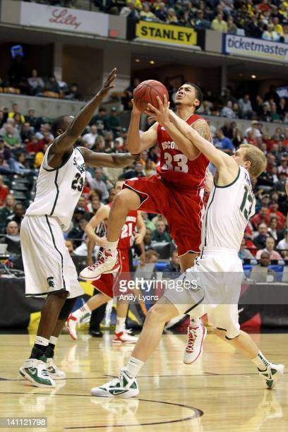 Rob Wilson of the Wisconsin Badgers drives for a shot attempt against Draymond Green and Austin Thornton of the Michigan State Spartans during their...