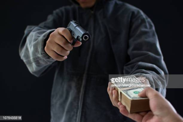 robbery with gun's. gun and money in a hands. bank robbery, man carrying a gun to rob the bank note. to threaten with the man. a murderer attacking holding gun kidnapping business young person. - marijuana money stock photos and pictures