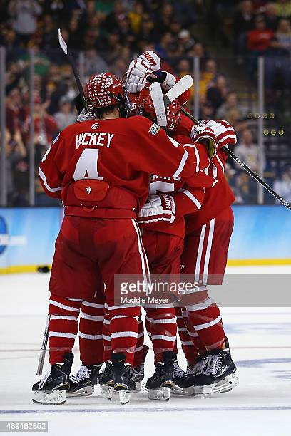 Robbie Baillargeon, Brandon Fortunato and Jack Eichel congratulate A.J. Greer of the Boston Terriers after he scored against North Dakota during the...