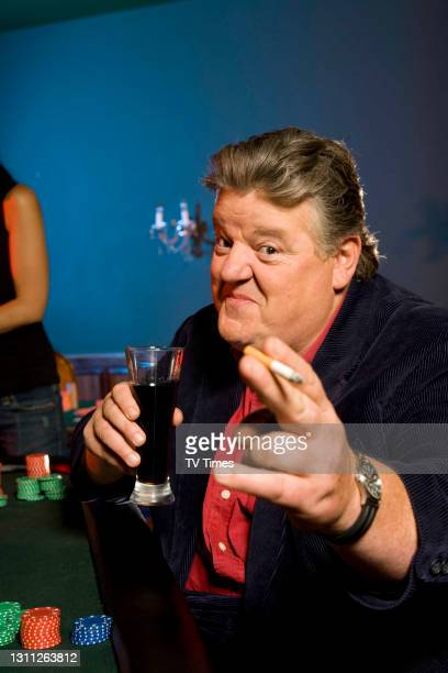Robbie Coltrane smiling drinking smoking posed Issue 45 2006.